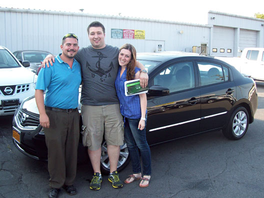 Stephanie Geoghegan and Dale Rexhouse with their 2012 Nissan Sentra, standing with sales consultant Joe Erps